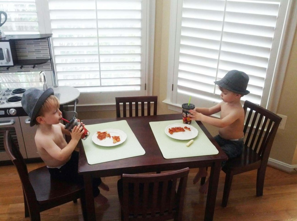 Twins with hats eating pizza with no shirts